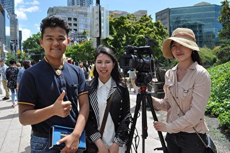 """图说:名叫Kei Takahashi的日本游客(左一),在温哥华""""720""""反迫害集会上了解了法轮功真相后,拍照留念,并竖起大拇指支持反迫害。(唐风/大纪元)"""