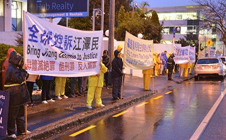 7月20日晚,近百名法輪功學員來到奧克蘭中領館,在風雨中無聲的抗議。(易凡/大紀元)