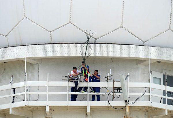 7月28日,台风尼莎来袭,新北市三貂角,工作人员在雷达站加强固定天线。(SAM YEH/AFP/Getty Images)