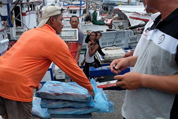 7月28日,台风尼莎来袭,宜兰县苏澳码头,渔船停泊在港湾,外劳在忙碌着整理物品。(SAM YEH/AFP/Getty Images)