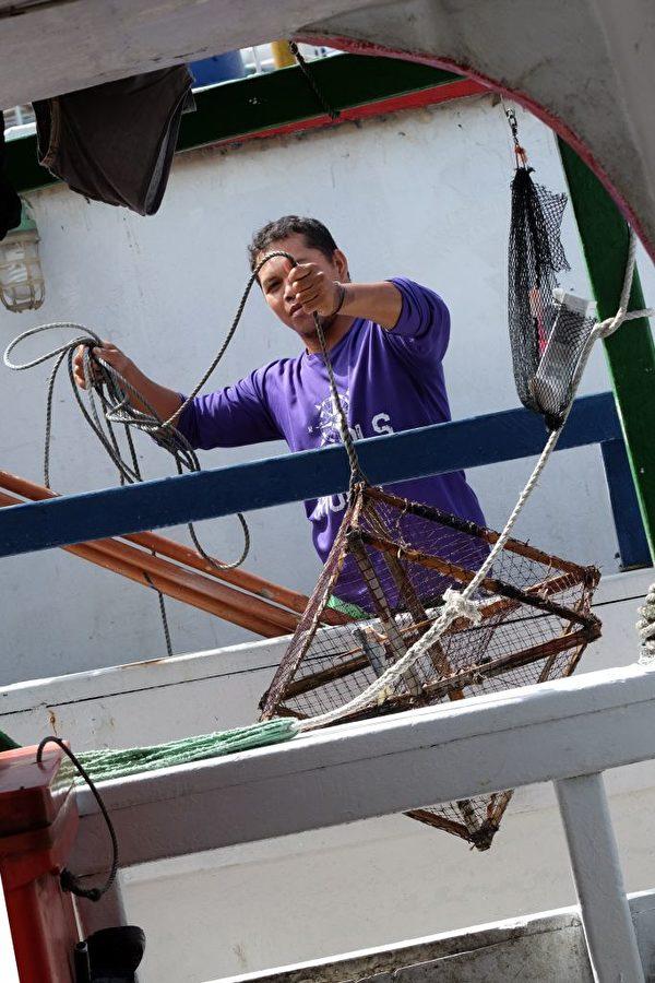 7月28日,台风尼莎来袭,宜兰县苏澳码头,一名印尼外劳在渔船上整理物品。(SAM YEH/AFP/Getty Images)