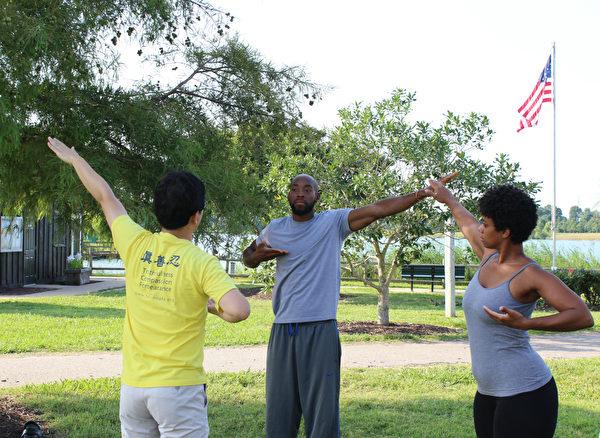 私人健身教練索耶(中)和兒童讀物作家漢金斯(右)在學煉法輪功功法動作。(林樂予/大紀元)