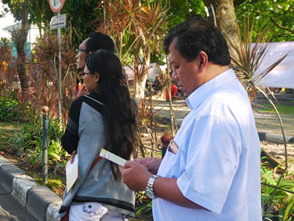 巴厘島當地民眾認真看法輪功學員傳遞的真相傳單。(蕭律生/大紀元)
