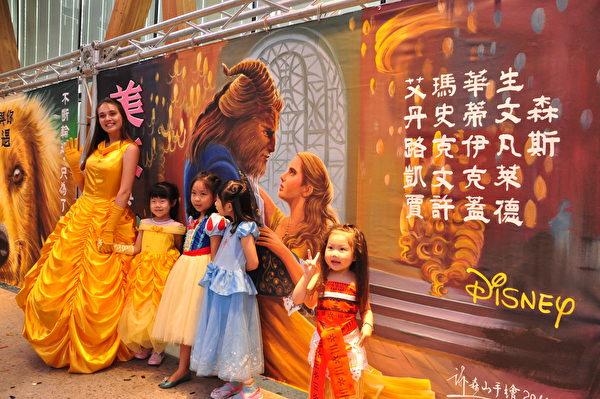 电影故事中的美女与可爱的小朋友在看板前合照。(赖月贵/大纪元)