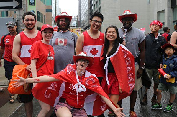 暴雨未能阻碍人们赶来庆祝加拿大150周年国庆的脚步,许多家庭冒雨来到国会山。(梁耀/大纪元)