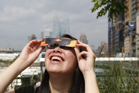 曼哈頓天際線下看日蝕的紐約人。