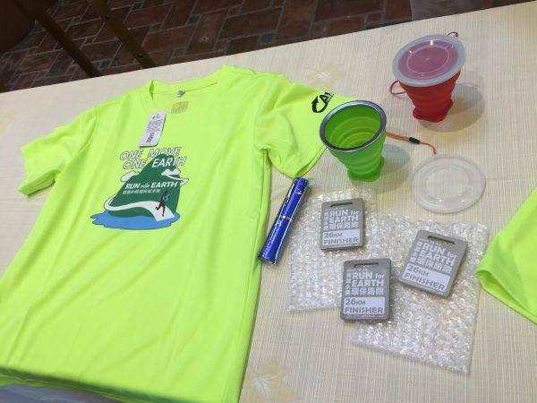 活动赠品有回收宝特瓶再制纤维制成的纪念衫、随手折叠杯、清水模复刻版设计的完赛奖牌。(宜县环保局提供)