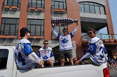 图:该市冰球队队员们在游行中向人们展示了他们获得的Fred Page Cup奖杯,与观众们分享他们的喜悦。(唐风/大纪元)