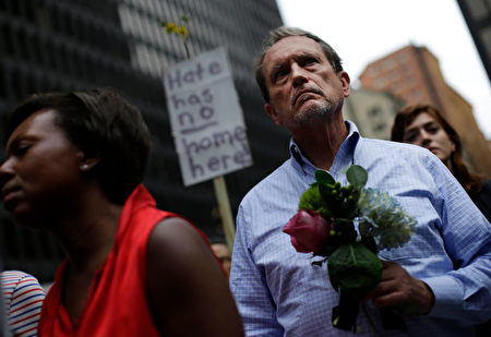 A man holds flowers at a vigil August 13, 2017 in Chicago, Illinois for the victims in the previous day's violent clashes in Charlottesville, Virginia. Heather Heyer was killed and 19 people were injured in the city of Charlottesville when a car plowed into a crowd of people after a rally by Ku Klux Klan members and other white nationalists turned violent. Two state police officers died in a helicopter crash near the area. / AFP PHOTO / Joshua Lott (Photo credit should read JOSHUA LOTT/AFP/Getty Images)