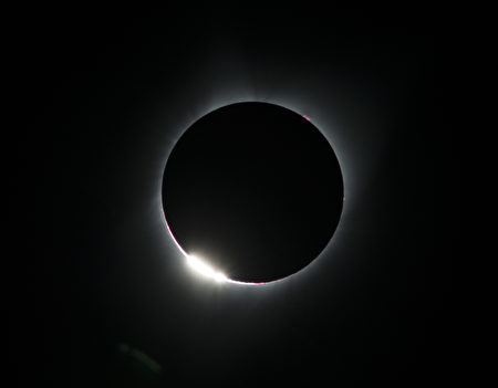 """TOPSHOT - The """"diamond ring effect"""" is seen during a total solar eclipse as seen from the Lowell Observatory Solar Eclipse Experience on August 21, 2017 in Madras, Oregon. Millions will be able to witness the total eclipse that will touch land in Oregon on the west coast and continue through South Carolina on the east coast. / AFP PHOTO / STAN HONDA (Photo credit should read STAN HONDA/AFP/Getty Images)"""