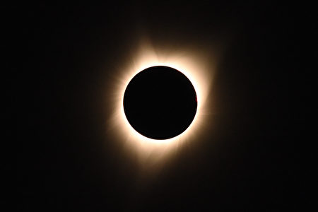 """The sun's corona is visible as the moon passes in front of the sun during a total solar eclipse at Big Summit Prairie ranch in Oregon's Ochoco National Forest near the city of Mitchell on August 21, 2017. The Sun started to vanish behind the Moon as the partial phase of the so-called Great American Eclipse began Monday, with millions of eager sky-gazers soon to witness """"totality"""" across the nation for the first time in nearly a century. / AFP PHOTO / Robyn Beck (Photo credit should read ROBYN BECK/AFP/Getty Images)"""
