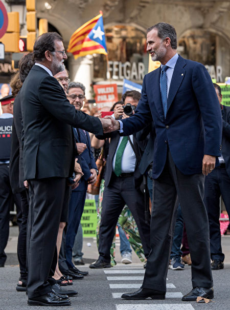 BARCELONA, SPAIN - AUGUST 26: King Felipe VI of Spain (R) shakes hands with Spain's Prime Ministre Mariano Rajoy as they arrive to a demonstration against the last week's terrorist attacks on August 26, 2017 in Barcelona, Spain. Hundreds of thousands people have marched in central Barcelona for the 'No tinc Por' (I am not afraid) joining in solidarity with the 14 victims of last week's terrorists attacks in Barcelona and Cambrils. 14 people were killed and dozens of injured in two terrorist attacks on August 17, when a van rammed crowds along the popular street of Las Ramblas in Barcelona and then a woman was sttabed by a terrorist in Clambrils. (Photo by David Ramos/Getty Images)