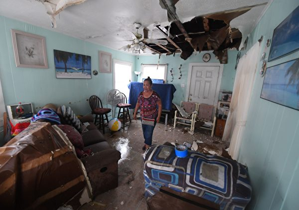 TOPSHOT - Celina Martinez returns to find her family home badly damaged after Hurricane Harvey hit Rockport, Texas on August 26, 2017. / AFP PHOTO / MARK RALSTON (Photo credit should read MARK RALSTON/AFP/Getty Images)