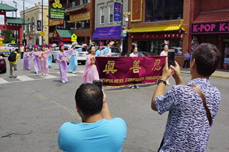 2017年8月5日,來自美國中部各州的部分法輪功學員在芝加哥中國城遊行,圖為路邊觀眾在用手機拍照。(David Yang/大紀元)