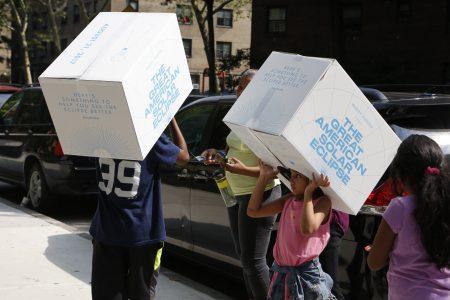 扛著紙箱抗日蝕的紐約兒童。