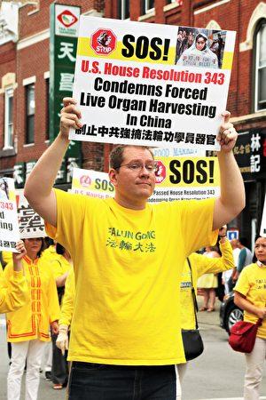 史蒂文斯走在遊行隊伍中,手舉呼籲制止中共強摘法輪功學員器官的標語板。(陳雷/大紀元)