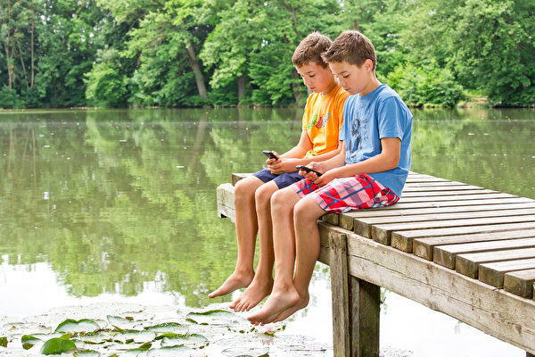 Two teenage friends with smartphones idyllic pond