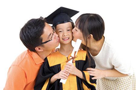 毕业典礼中,亚洲幼儿园的毕业生和迫击炮孩子由她的父母亲吻。(fotolia)