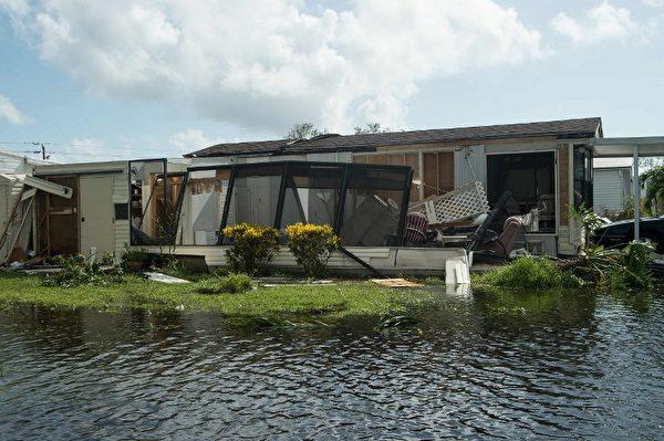 佛羅里達州那不勒斯洪水淹沒的街道上受損的房屋。( AFP PHOTO / NICHOLAS KAMM)
