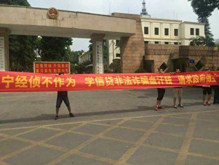 来自大陆各地数十名学信贷平台投资人在广西自治区政府门前静坐、打横幅维权。(受访者提供)
