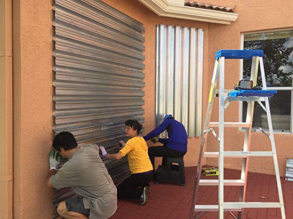 林夫婦和朋友在裝颶風百葉窗。(吳蔚溪/大紀元)