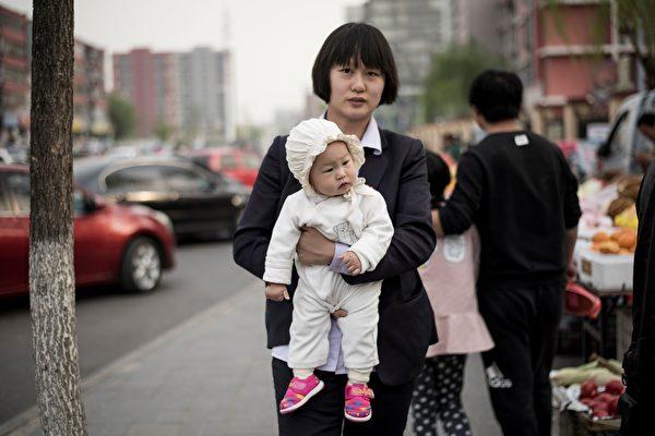 中國式父母試圖為孩子鋪墊一切。圖為2017年4月13日,北京順義街頭一名抱孩子的母親。(FRED DUFOUR/AFP/Getty Images)