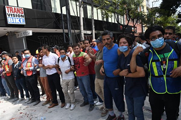 9月19日墨西哥城發生7.1級強震,至少上百人遇難。圖為當地志願者在地震現場圍起一道人牆,避免他人進入瓦礫中和危險地段。(ALFREDO ESTRELLA/AFP/Getty Images)