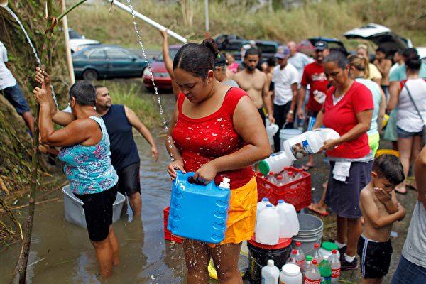 波多黎各居民排队接山泉水。(RICARDO ARDUENGO/AFP/Getty Images)