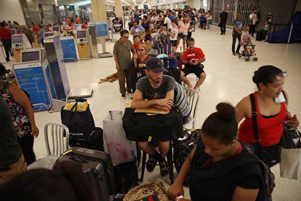 旅客在圣胡安市内的机场大排长龙,等待一位难求的机位。(Joe Raedle/Getty Images)