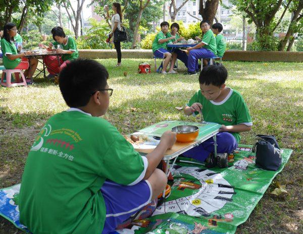 """学生在校园一隅的大树下,摆上户外餐桌椅或野餐垫与手作餐垫,享受幸福""""食""""光。(方金媛/大纪元)"""