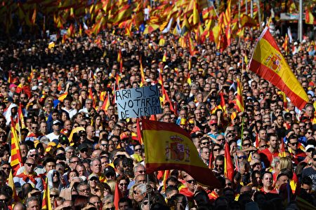 """A protester holds a sign reading """"Now yes, yes, we will vote for real"""" amid a wave of Spanish flags during a pro-unity demonstration in Barcelona on October 29, 2017. Pro-unity protesters were to gather in Catalonia's capital Barcelona, two days after lawmakers voted to split the wealthy region from Spain, plunging the country into an unprecedented political crisis. / AFP PHOTO / LLUIS GENE (Photo credit should read LLUIS GENE/AFP/Getty Images)"""