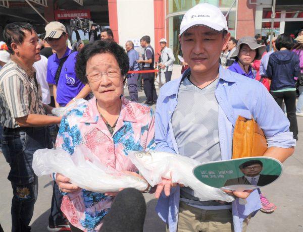 虱目魚拍賣,謝姓母子早上8點就來排隊,以20元搶購市價一條上百元的虱目魚。(方金媛/大紀元)