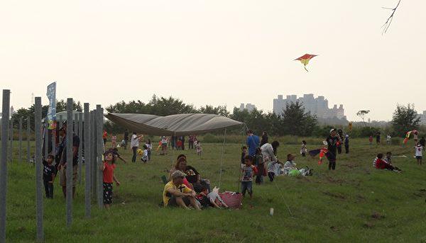 在秋日悠閒午後,民眾大手牽小手一起放風箏,享受舒爽的親子時光。(曾晏均/大紀元)