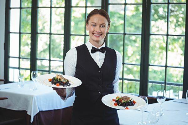 Smiling waitress holding plates