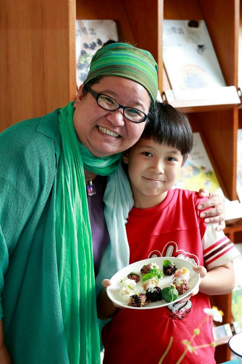"""马爱云(左)为小学生们推动""""食育料理教学""""。(马爱云提供)"""