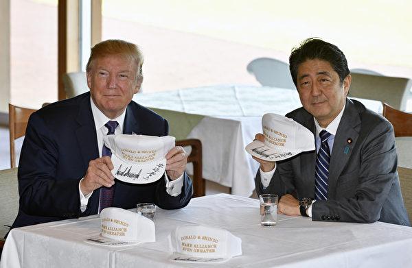 美國總統川普(特朗普)伉麗11月5日訪問日本,日本首相安倍晉三安排兩人一起打高爾夫球和進餐,向外界展現兩國堅定的盟友關係和密切的私人關係。圖為兩人在高爾夫球俱樂部交換簽名帽。(FRANCK ROBICHON/AFP)