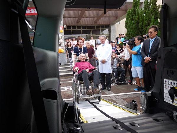 资深媒体人黄宝慧(如图)捐车给台中荣总嘉义分院,该车配备有国产唯一电动辅助牵引机,在捐车仪式中,她示范推着坐在轮椅上的父亲准备上车。(台中荣总嘉义分院提供)