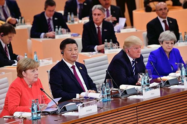 今年7月7日的G20會議上,東道主德國總理默克爾旁邊是中國主席習近平、美國總統川普和英國首相梅。(Thomas Lohnes/Getty Images)