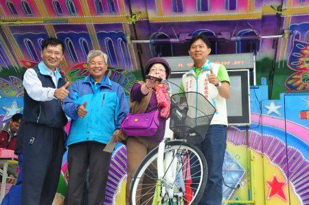摸到自行车大奖,来个开心合影,右1为新竹县农业处长邱世昌、左1为农村再生执行长范振龙 。(赖月贵/大纪元)
