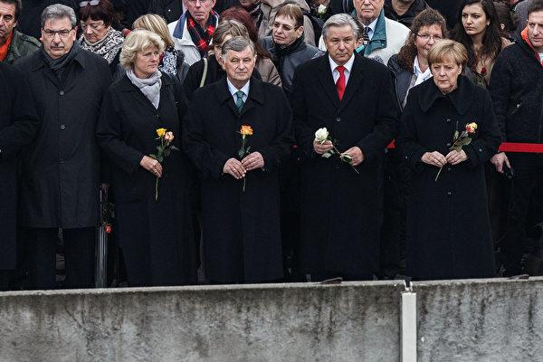 2014年11月9日,在柏林墙倒塌25周年的纪念仪式上,德国总理默克尔与其他政要一起,在柏瑙尔街围墙纪念馆向残留的柏林墙置放玫瑰。(Carsten Koall/Getty Images)