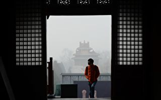 TOPSHOT - A man wearing a mask visits the Forbidden City in Beijing on December 21, 2016. Beijing issued its first air pollution red alert for 2016 on December 15, with choking smog expected to cover the city and surrounding areas in north China until December 21. / AFP / WANG ZHAO (Photo credit should read WANG ZHAO/AFP/Getty Images)
