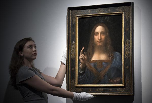 2017年10月24日,佳士得的一位工作人員在倫敦預展上手扶達·芬奇畫作《救世主》。(Carl Court/Getty Images)