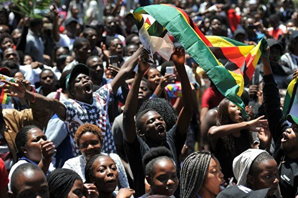 TOPSHOT - A man holding a flag of Zimbabwe takes part in a demonstration of University of Zimbabwe's students, on November 20, 2017 in Harare, to demand the withdrawal of Grace Mugabe's doctorate and refused to sit their exams as pressure builds on Zimbabwe's President Robert Mugabe to resign.<br /> Zimbabwe's President faced the threat of impeachment by his own party on November 20, 2017, after his shock insistence he still holds power in Zimbabwe despite a military takeover and a noon deadline to end his 37-year autocratic rule.<br /> / AFP PHOTO / - (Photo credit should read -/AFP/Getty Images)