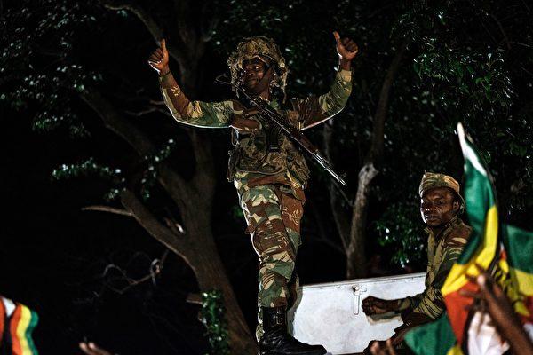 津巴布韦总统穆加贝周二(11月21日)辞职,结束了对津国长达37年的统治。图为民众和士兵在庆祝。(AFP PHOTO / MARCO LONGARI (Photo credit should read MARCO LONGARI/AFP/Getty Images)
