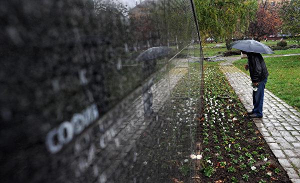 图为2009年11月10日,在保加利亚首都索非亚,一名男子在写有两万名共产党统治时期受难者的纪念碑前寻找亲人的名字。共产党曾统治保加利亚45年,今天已不复存在。(DIMITAR DILKOFF/AFP/Getty Images)