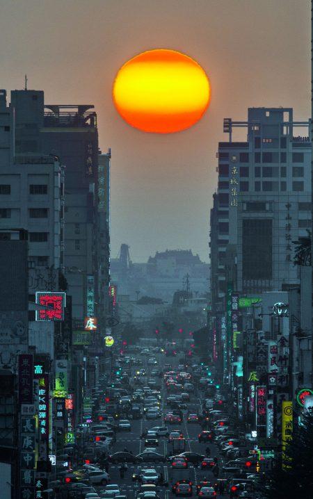 """美国纽约曼哈顿的""""悬日""""奇景,是指太阳下山时,身影恰巧落在两栋玻璃帷幕大楼之间,夕阳余晖把街道渲染成金色童话大道,这样有如电影场景的自然城市美景在高雄也能捕捉到。图为今年1月高雄青年路落日美景。(张忠义提供)"""