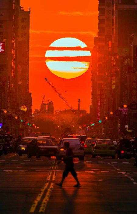 """美国纽约曼哈顿的""""悬日""""奇景,是指太阳下山时,身影恰巧落在两栋玻璃帷幕大楼之间,夕阳余晖把街道渲染成金色童话大道,这样有如电影场景的自然城市美景在高雄也能捕捉到。图为今年1月在青年路的落日美景。(张忠义提供)"""