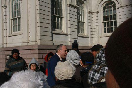 街頭小販們在市政廳前攔住議員崔馬克,請他支持增加許可證數量。