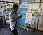 近日,大陆互联网服务商支付宝、芝麻信用、百度 APP非法获取公民信息,侵犯用户隐私一事引发关注。图为北京一家商店张贴支付宝移动支付服务的横幅。(AFP PHOTO / WANG ZHAO)