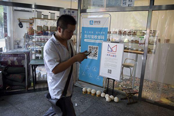 2011年,阿里支付寶股權之爭,暴露出VIE的潛在風險。圖為北京一家商店張貼支付寶流動支付服務的橫幅。(AFP PHOTO/WANG ZHAO)